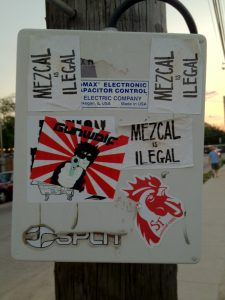 "Stickers reading ""Mezcal is Ilegal"" on a telephone pole near Clives in Austin, TX."