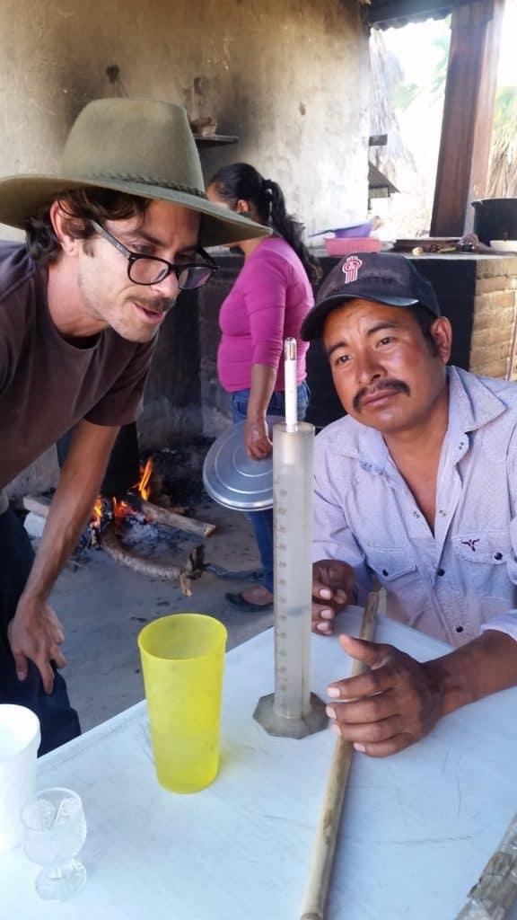 A photo of NETA co-founder Max Rosenstock as he discusses and upcoming batch of mezcla with maestro mezcalero Eliazar Garzia Vasquez.